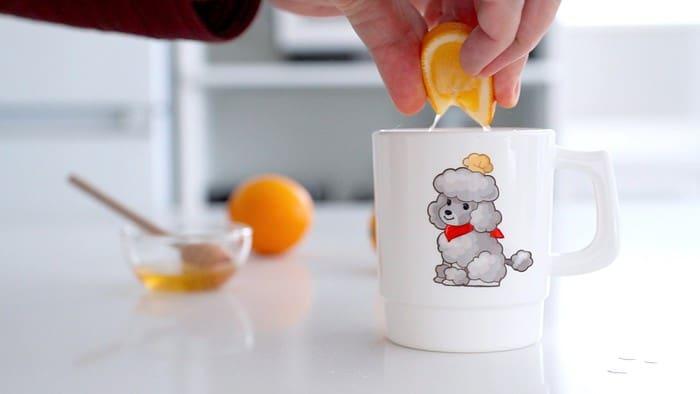 Squeezing lemon into ginger tea.