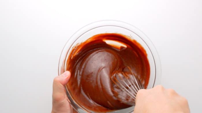 Whisking sugar and vanilla into the egg, chocolate and butter mixture.