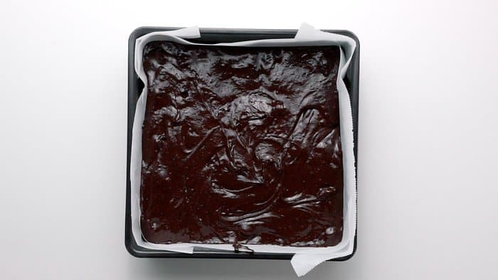 Fudgy brownie batter in a parchment lined brownie pan.