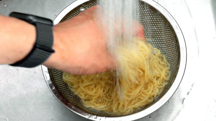 Washing boiled ramen noodles under cold running water.
