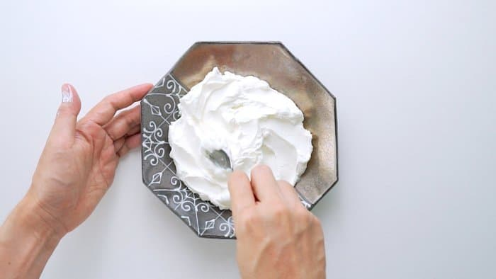 Spreading Labneh around a serving dish with s spoon.