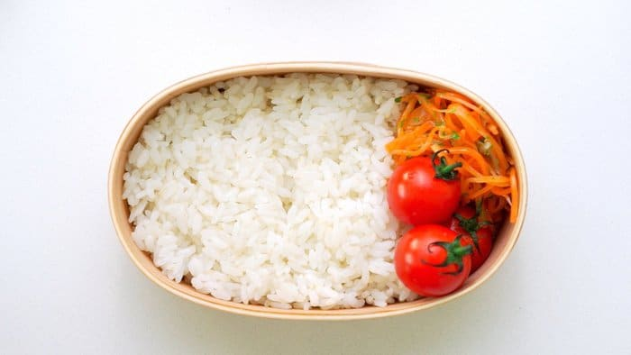 Rice, cherry tomatoes and carrot salad packed into a bento box.