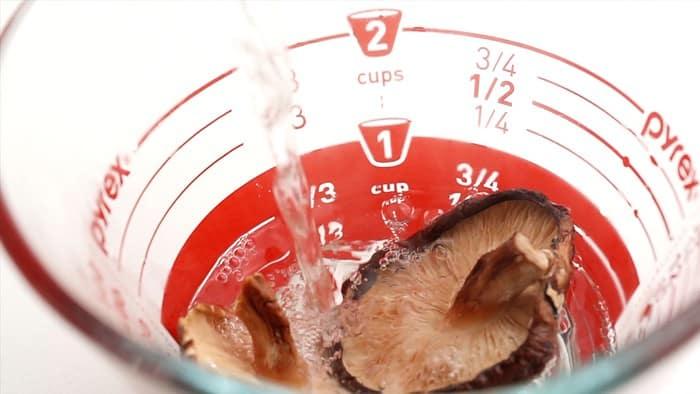 Rehydrating dried shiitake mushrooms in boiling water.