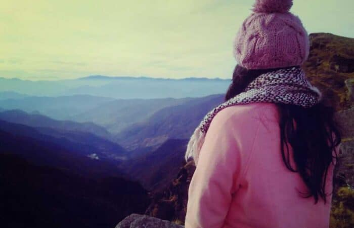 A girl looking mountains from Tungnath in Chopta Valley during summer season