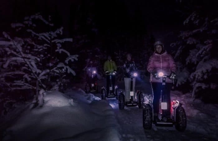 Segway Fahrer im tiefverschneiten Wald im Dunkel