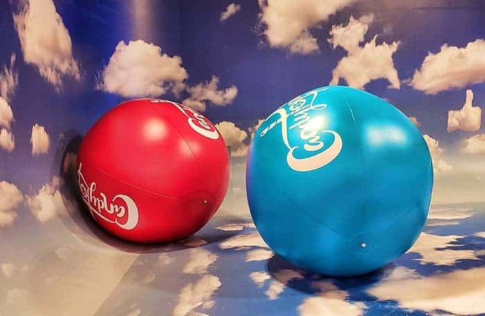 Extra large red and blue Candytopia balls on a cloud carpet