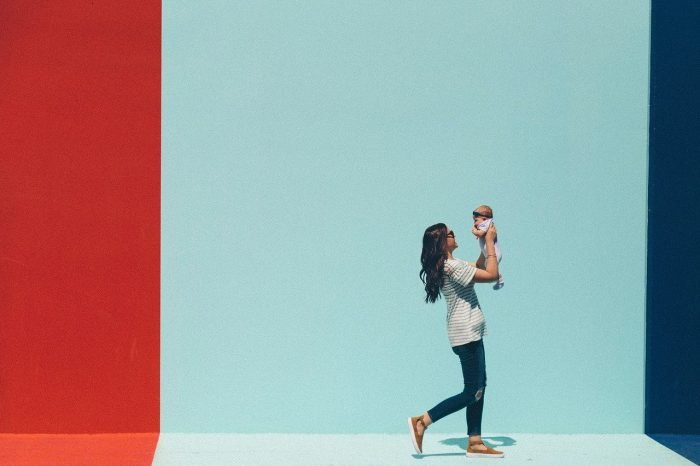 Woman carrying baby while walking mural