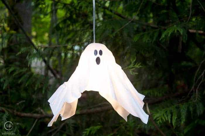 plastic white diy hanging ghost lantern hanging in a tree and turned on