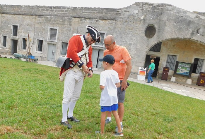 A volunteer shows a boy and dad the cochineal bugs that made red dye for colonial uniforms.