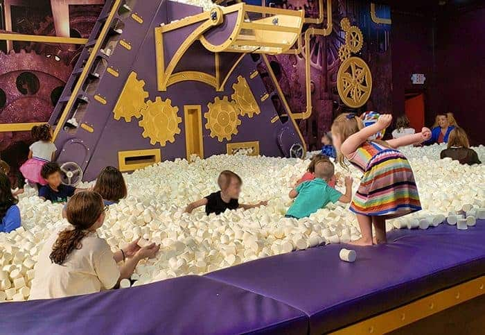 A giant marshmallow pit at Candytopia with people playing and a little girl about to jump in