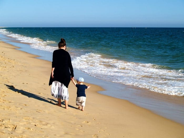 Woman and baby walking on sand seashore