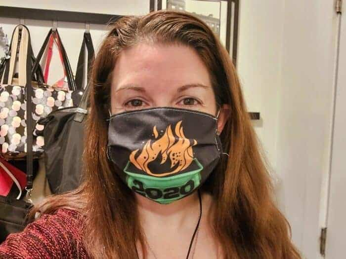 Amy wearing a mask with a flaming dumpster on it