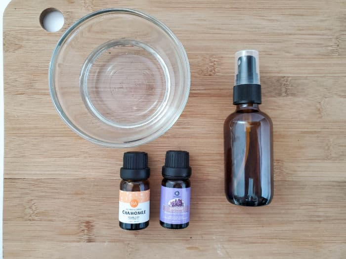 Bowl of water, spray bottle and essential oil bottles on a wood board.