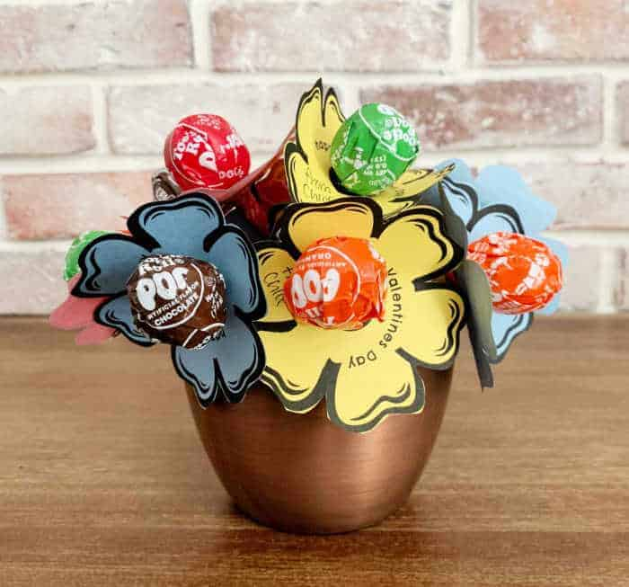 lollipop bouquet on a wood table with brick wall in the background.