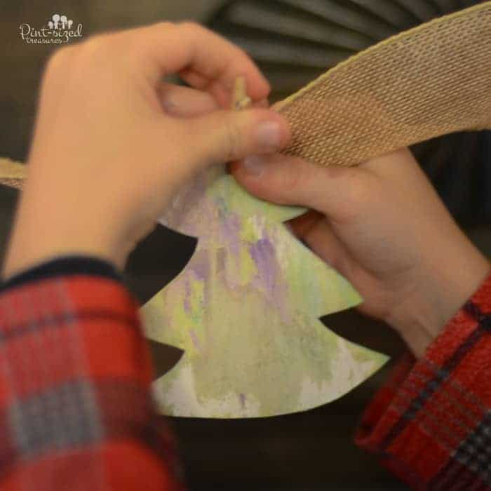 childs hands pinning a paper tree onto burlap ribbon