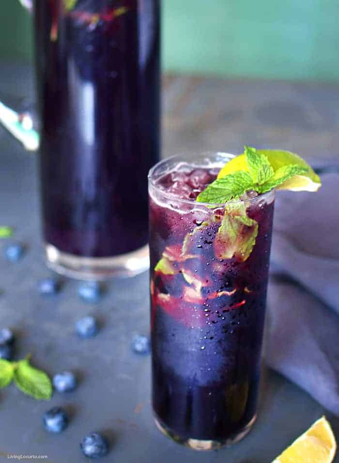 Blueberry Mojito Pitcher Recipe - Tall glass of dark purple mojito with mint and a lime.