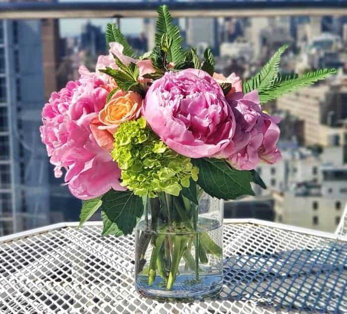 A vase of flowers on an outside table in front of a blurry view of Manhattan