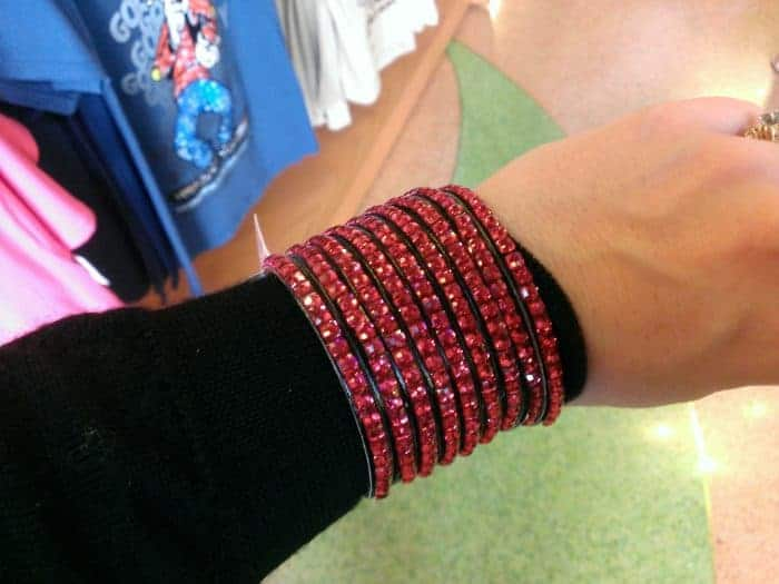 Red sparkly bracelet on my arm in The Disney Store