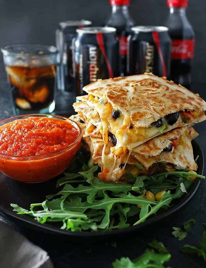 Photo of cheesy veggie quesadillas with roasted red pepper salsa and Coca-Cola in background