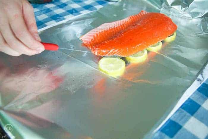 salmon in foil on top of lemons
