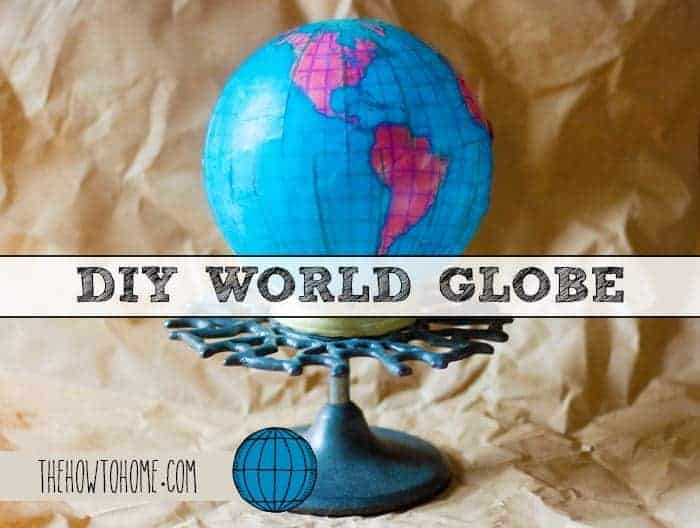 Pretty DIY Globe made with a white glass globe light fixture from the thrift store sitting on top of an antique rubber stamp holder with the text DIY World Globe across the mid center of the photograph