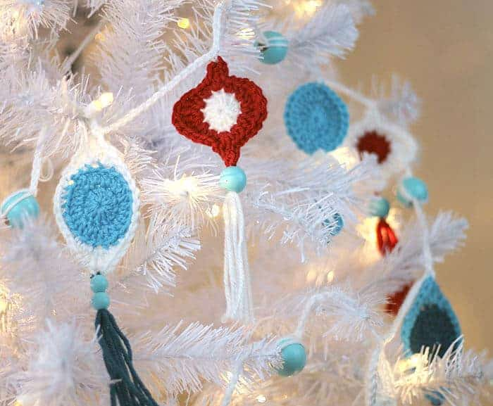 white christmas tree with crochet ornaments hanging from it
