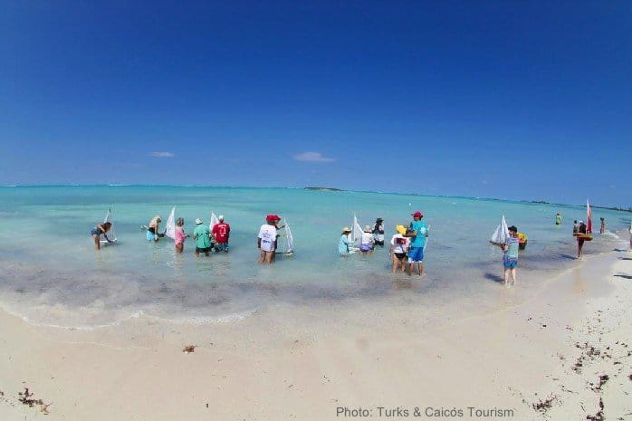 Kids and adults sailing toy boats on a beach in the turks & caicos