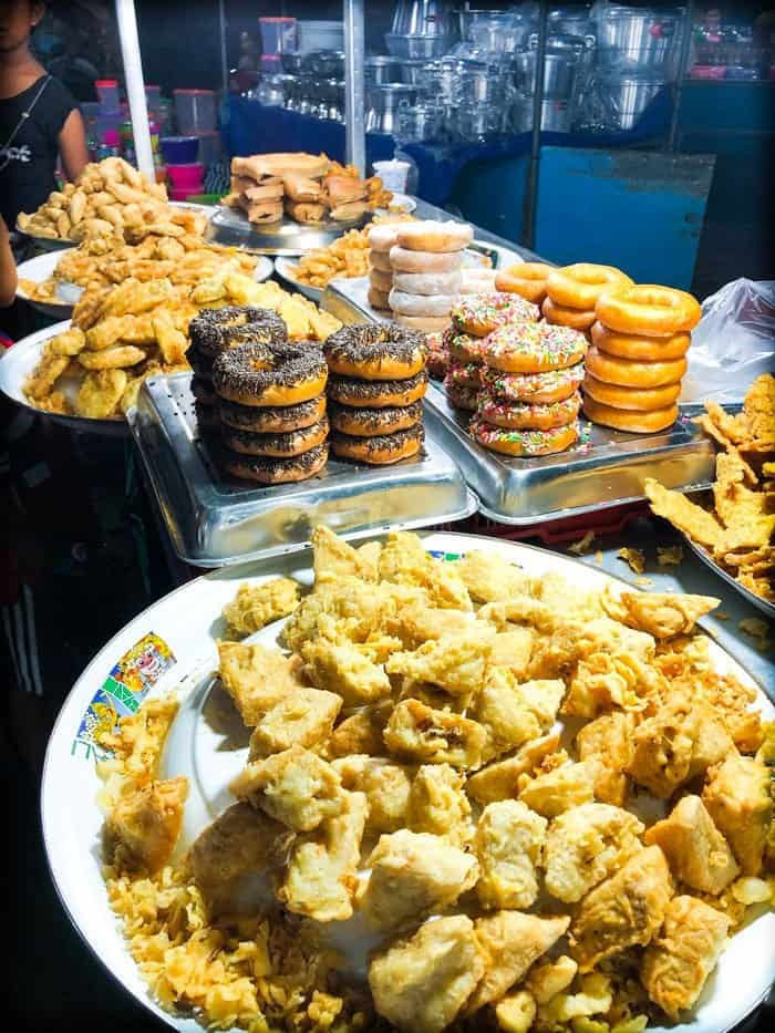 Fried treats, fried doughnuts, and fried tempe on sale at a food stall at a Bali night market in Gianyar, Indonesia