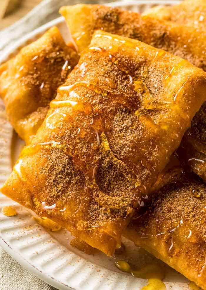 sopapillas on a white plate drizzled with cinnamon and honey