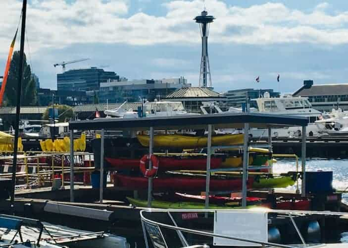 A stack of kayaks on lake union in seattle with the space needle in the background.
