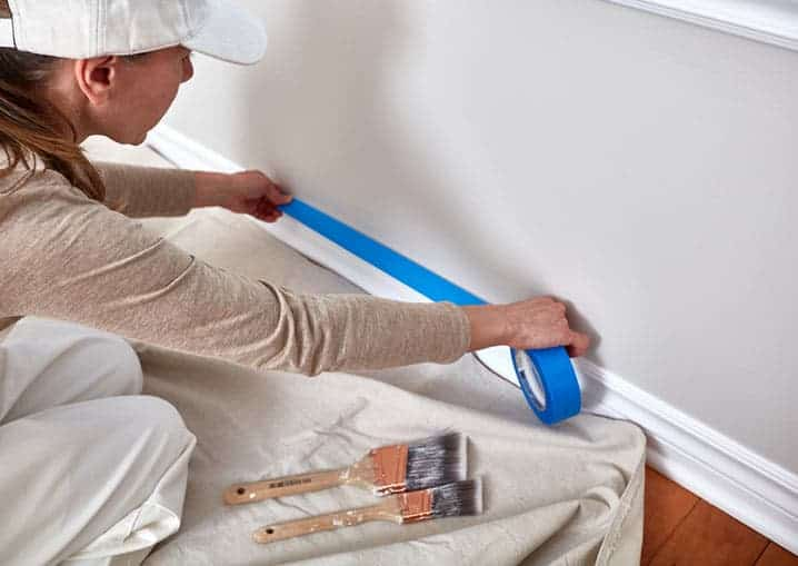 painter masking a room to prepare for painting