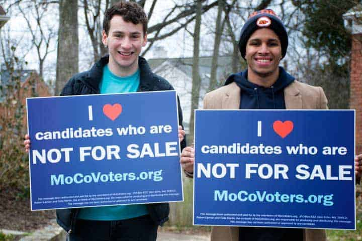 "young men holding signs that say ""I love candidates who are not for sale"""