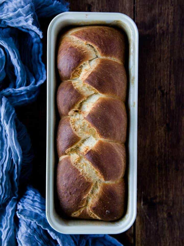 A loaf of brioche bread inside a tin with a blue cloth on the left side of the image