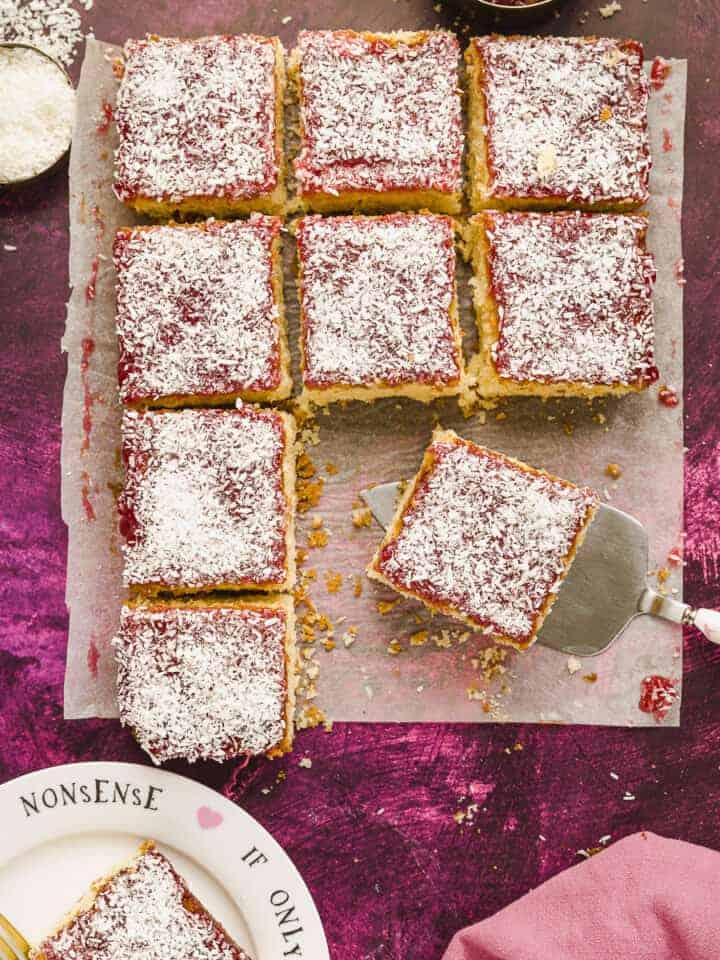 Squares of jam and coconut sponge cake on a pink background.