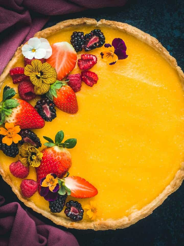 alemon tart coveredwith fresh fruit and edible flowers.