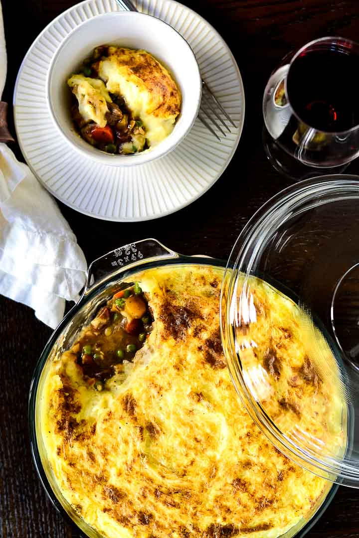 Overhead shot of classic lamb shepherd's pie. On the bottom of the photo is the glass serving dish with one portion missing, while at the top is a single serving in a white bowl and a glass of red wine.