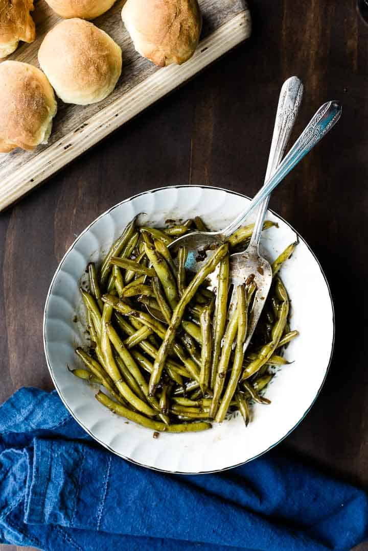 Overhead shot of worcestershire green beans in a white serving bowl next to a blue towel.