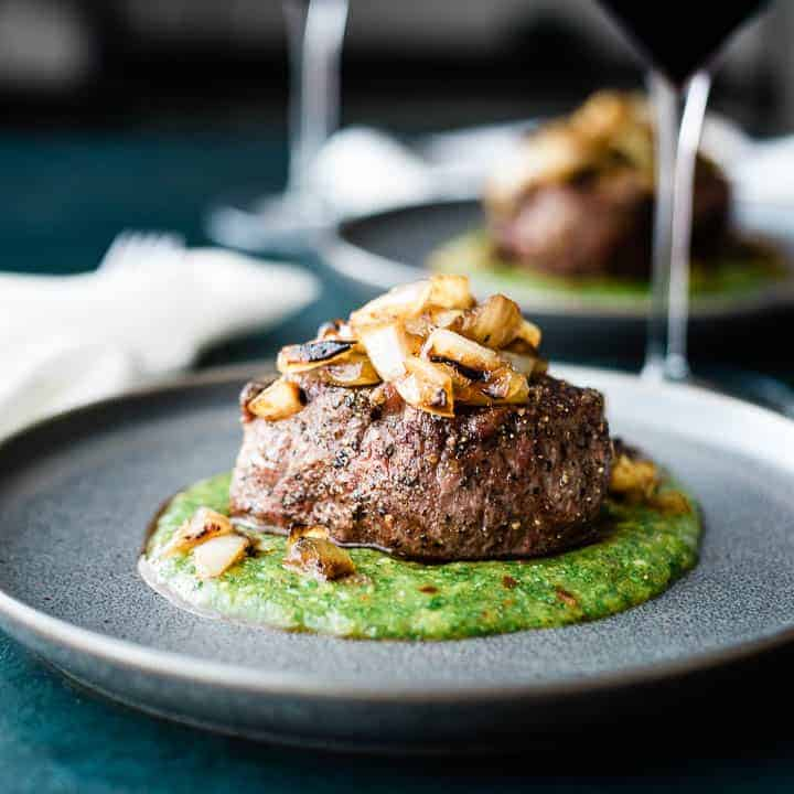 A thick cut filet mignon, resting on a green colored peach mango cilantro sauce and topped with grilled onions.