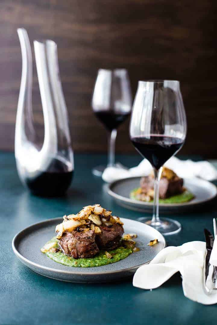 A thick cut filet mignon, resting on a green colored peach mango cilantro sauce and topped with grilled onions. A second serving is in the background along with a decanter of red wine and two glasses.