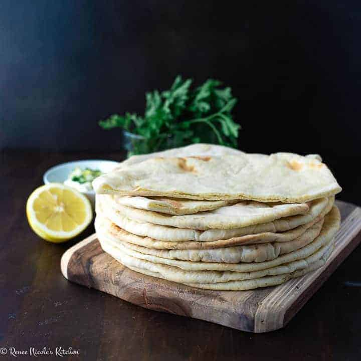 A stack of thin puffed pita bread on a wooden cutting board next to a bowl of tzatziki sauce, a sliced lemon, and a bunch of parsley.