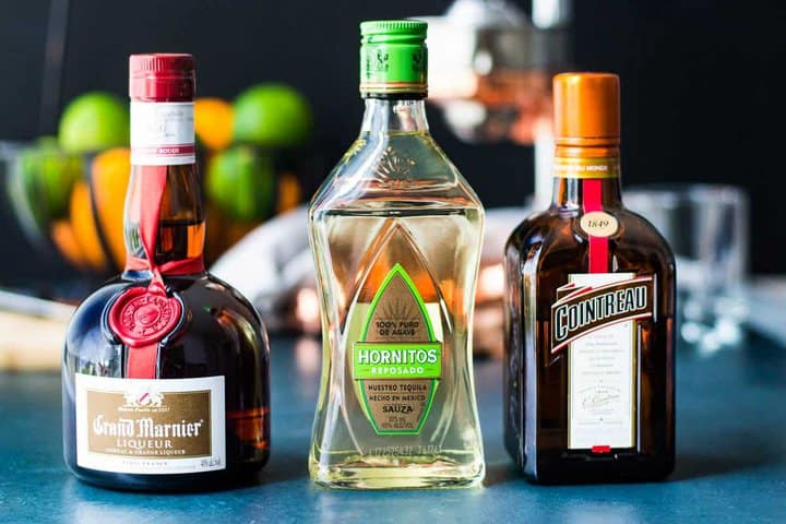 The three liquors for a cadillac margarita - grand marnier, reposado tequilla, and cointreau in front of a basket of citrus fruit.