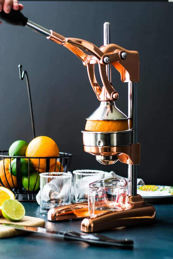 Tall copper citrus juicer, juicing an orange into a measuring cup in front of prepared rocks glasses with a bowl of citrus in the background.