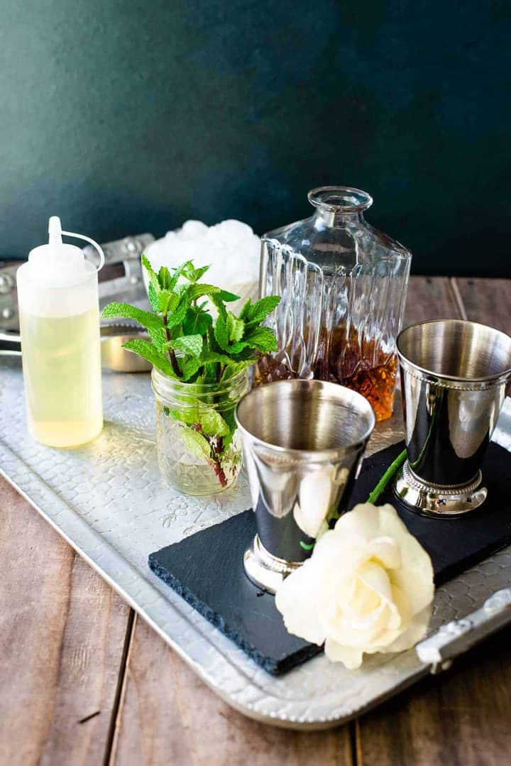 The set up for a Kentucky Derby Mint Julep bar on a silver tray. Mint, mint simple syrup, ice, bourbon, and julep cups.