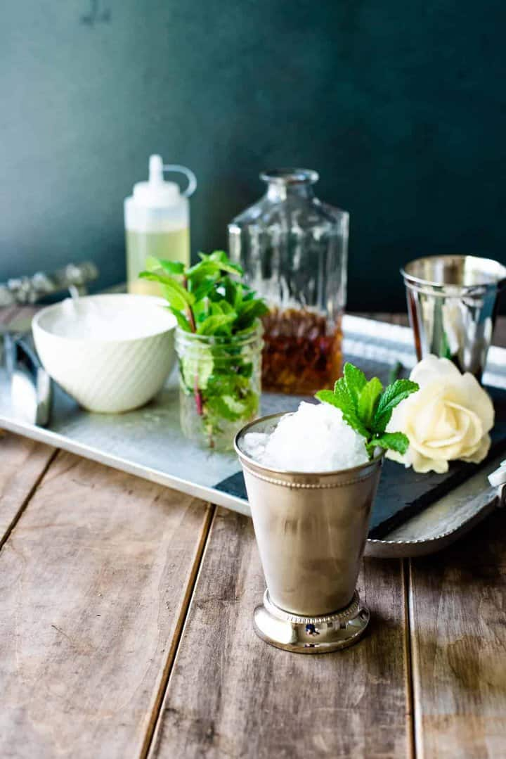 A finished mint julep in front of a silver tray set up with all you need to make a Kentucky Derby mint julep bar.