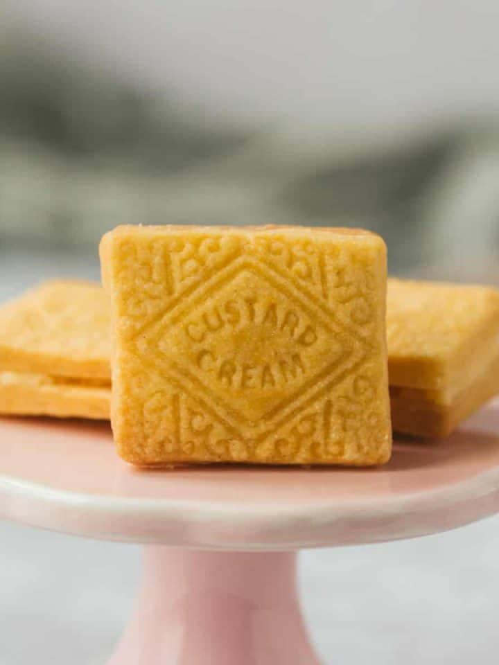 A homemade Custard Cream on a small pink stand.