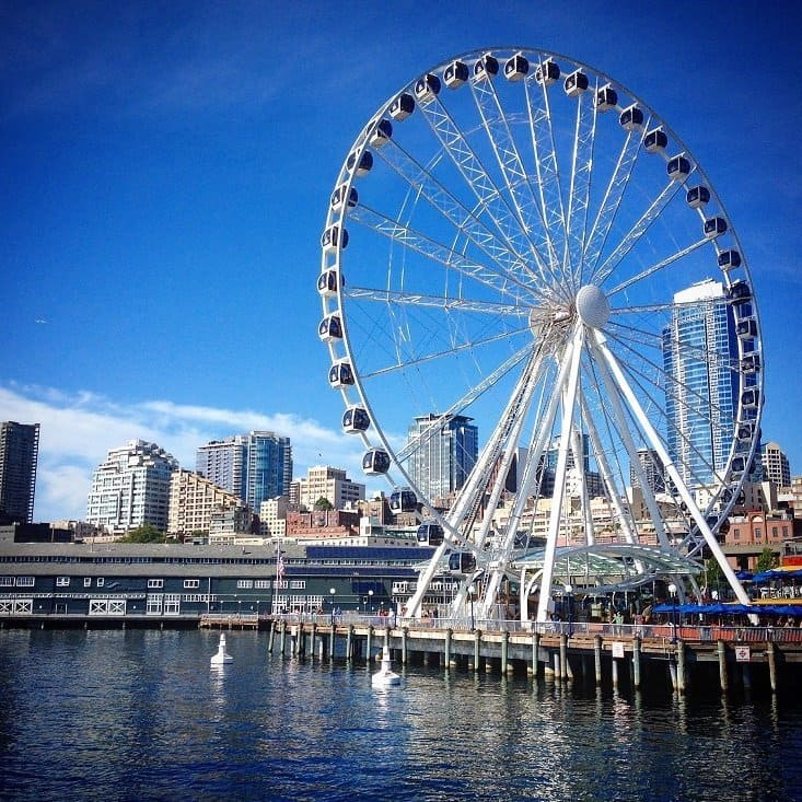 A large white ferris wheel sits on a dock, with a city skyline in the background. This is the Seattle Great Wheel, one of the activities in Seattle for families and tourists.