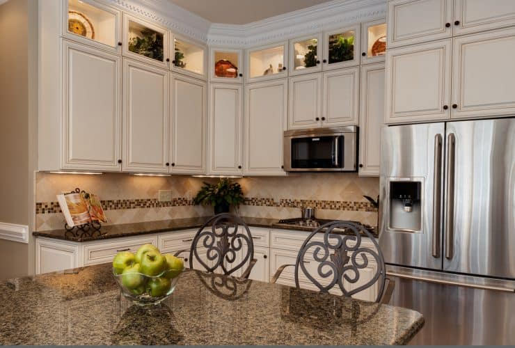 a traditional kitchen with the combo of glazed white cabinets and tropic brown granite