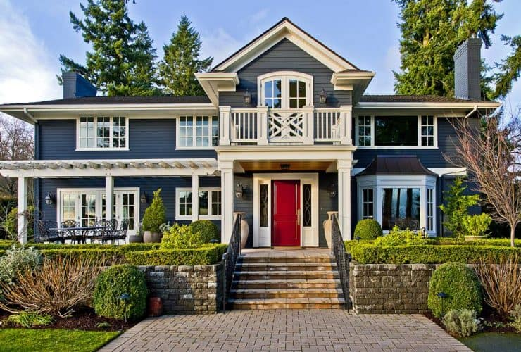 a traditional house with a timeless combination of denim blue wall and ruby red door