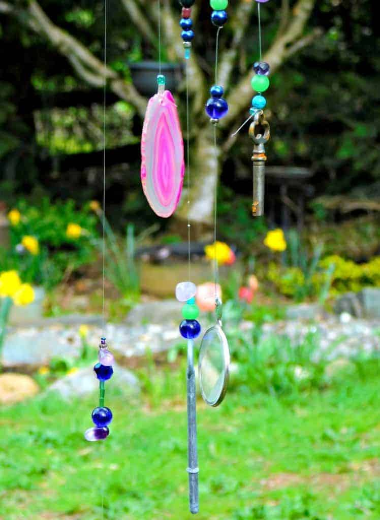 beads keys and stones hanging from wind chime in garden