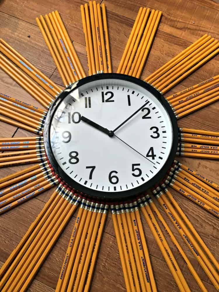 school clock with pencils around it grouped together